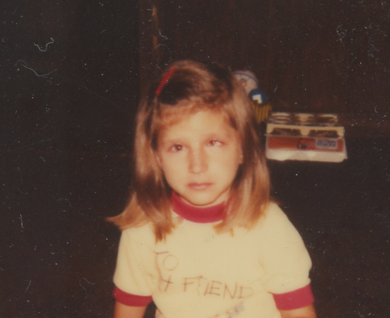 Young Girl with brown hair. Eyes appear crossed.  She is not smiling wearing a yellow and red ring tee